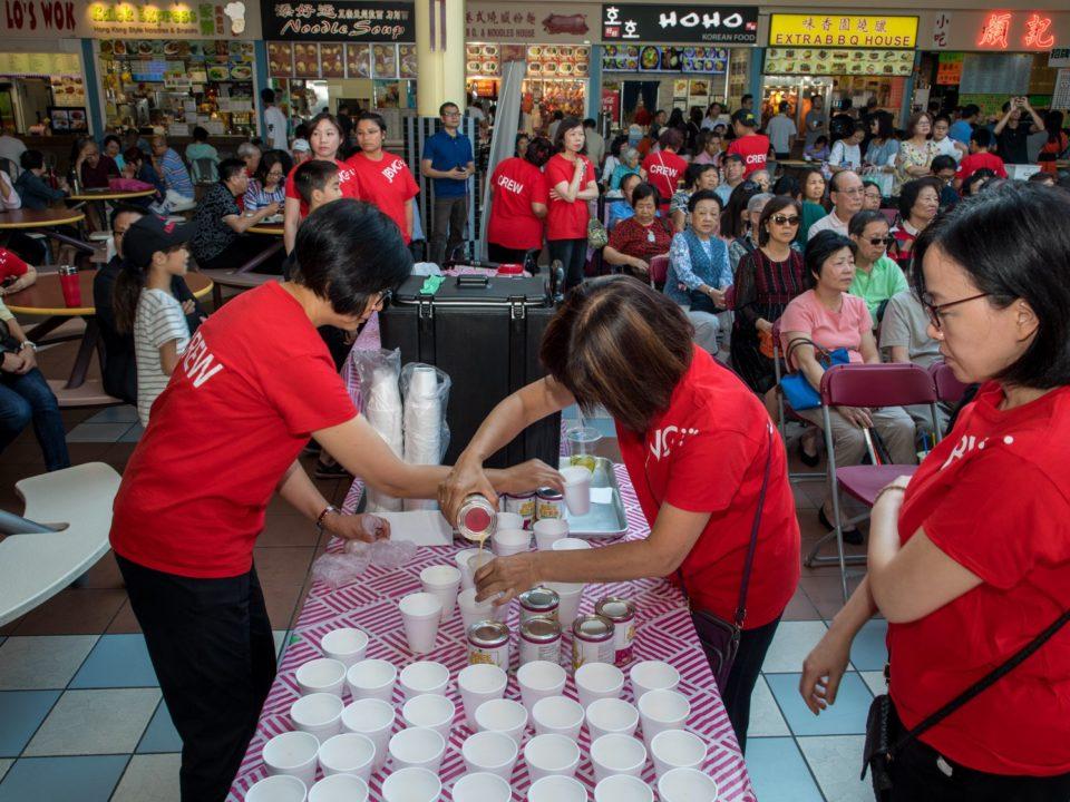 Volunteers preparing many cups of milk tea before serving